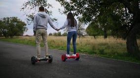 Jonge man en vrouw die op Hoverboard in het park berijden inhoudstechnologieën een nieuwe beweging Sluit omhoog van Dubbel Wiel stock video