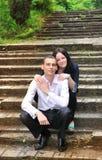 Jonge man en vrouw die in parkzitting omhelzen op achtergrond van oude trap. Stock Afbeeldingen