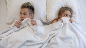 Jonge man en vrouw die pijnlijk vóór eerste intimiteit in bed, onzekerheid kijken stock afbeeldingen