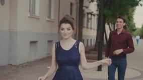Jonge man en vrouw die pret hebben De knappe mens probeert de achterstand inloopt mooi meisje stock video