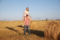 Jonge man en vrouw die pret op een geoogst gebied hebben dichtbij een baal van hooi Royalty-vrije Stock Foto