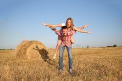 Jonge man en vrouw die pret op een geoogst gebied hebben dichtbij een baal van hooi Stock Afbeelding