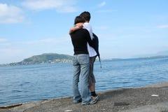 jonge man en vrouw die zich bij de kust bevinden en het overzees bekijken stock afbeelding