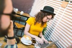 Jonge man en vrouw in glazen met laptop in koffie Royalty-vrije Stock Afbeeldingen