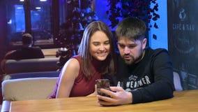 Jonge man en vrouw in koffie die nieuwe toepassing op slimme telefoon gebruiken Het glimlachen gelukkige, toevallige tienerjaren stock footage
