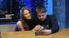 Jonge man en vrouw in koffie die nieuwe toepassing op slimme telefoon gebruiken Het glimlachen gelukkige, toevallige tienerjaren stock video