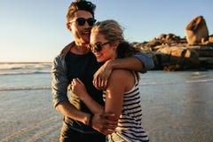 Jonge man en vrouw in liefde op kust stock afbeelding