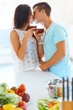 Jonge man en vrouw met rode wijn het kussen in de keuken Stock Afbeeldingen