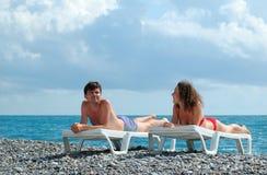 Jonge man en vrouw op strand Stock Foto's