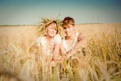Jonge man en vrouw op tarwegebied Stock Foto's