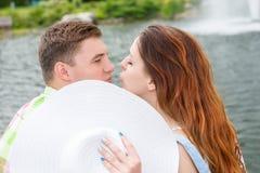 Jonge man en vrouwen het kussen het verbergen achter de hoed Stock Fotografie