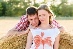 Jonge man en vrouwen het stellen op een gebied dichtbij een baal van hooi Royalty-vrije Stock Fotografie