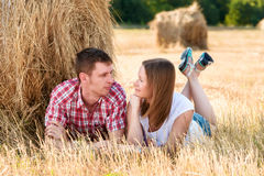 Jonge man en vrouwen het stellen op een gebied dichtbij een baal van hooi Royalty-vrije Stock Foto's