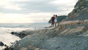 Jonge man en vrouwen kussen die zich op strand op de zomeravond bevinden stock video