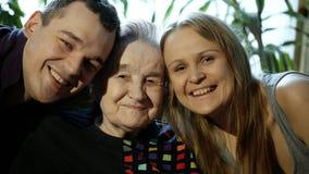 Jonge man en vrouwen kussende grootmoeder op wangen stock footage