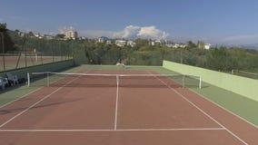 Jonge man en vrouwen speeltennis in sporttoevlucht, panorama van hof stock videobeelden