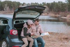 Jonge man en vrouwenzitting in open boomstam van auto dichtbij de de rivier en het letten op wegenkaart royalty-vrije stock foto's