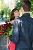 Jonge man gift een vrouw een boeket van rode rozen in een de zomerpark stock foto's