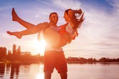 Jonge man holdingsvrouw op de bank van de de zomerrivier Paar die pret hebben bij zonsondergang Kerels het koelen stock afbeeldingen