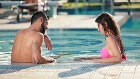 Jonge man met baard en het mooie vrouw ontspannen in het zwembad stock videobeelden