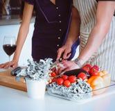Jonge man scherpe groenten en vrouw die zich in de keuken bevinden Royalty-vrije Stock Fotografie