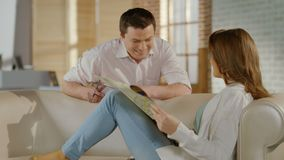 Jonge man, vrouw die kaart, het spreken, de vakantie van de planningsfamilie controleren stock video