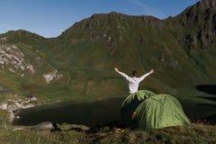 Jonge man wapens die voor een groene tent in de bergen van Zwitserland worden opgeheven terwijl hij van het panorama geniet stock foto