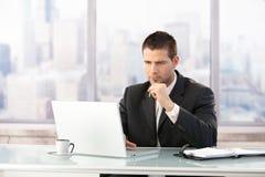 Jonge manager die aan laptop in bureau werkt Stock Foto's