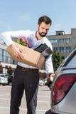 jonge manager met doos van persoonlijke materiaal het openen autoboomstam royalty-vrije stock foto