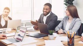 Jonge managers die grafieken en grafieken analyseren op vergadering stock afbeeldingen