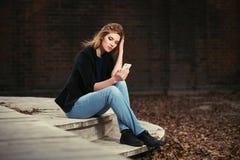 Jonge manier bedrijfsvrouw die slimme telefoon op stadsstraat met behulp van Stock Afbeeldingen