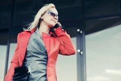 Jonge manier bedrijfsvrouw die in zonnebril celtelefoon uitnodigt Stock Afbeelding