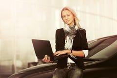 Jonge manier bedrijfsvrouw met laptop naast haar auto Stock Fotografie