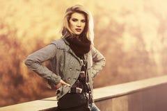 Jonge manier blonde vrouw die gecontroleerde plaidblazer in stadspark dragen stock afbeeldingen