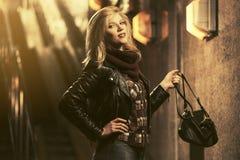 Jonge manier blonde vrouw die leerjasje in een metro dragen stock afbeeldingen