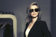 Jonge manier blonde vrouw in zonnebril in het wandelgalerijbinnenland stock afbeelding