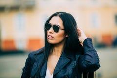 Jonge manier donkerbruine vrouw in zonnebril met jasje Stock Foto's