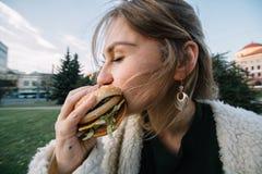 Jonge manier grappige vrouw die hamburger openlucht op de straat eten Stock Foto's