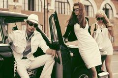 Jonge manierman en vrouwen door retro auto Royalty-vrije Stock Fotografie