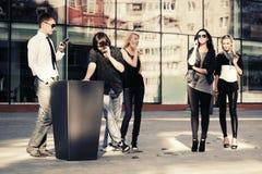 Jonge maniermannen en vrouwen die mobiele telefoons uitnodigen stock afbeelding