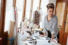 Jonge manierontwerper op het werk, Afrikaanse vrouw die aan iemand kijken stock afbeelding