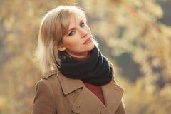 Jonge maniervrouw die in beige laag in de herfstpark lopen royalty-vrije stock afbeeldingen