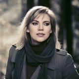 Jonge maniervrouw die in beige laag in het park van de de herfststad lopen royalty-vrije stock fotografie