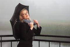 Jonge maniervrouw met paraplu die op leuning in een mist leunen Stock Afbeeldingen