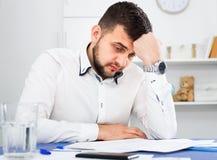 Jonge mannelijke arbeider die probleem in project in bureau hebben royalty-vrije stock foto's