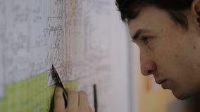 Jonge mannelijke architect die bij tribuneplan met een heerser en pen, die afstand een meten aan plan werken stock videobeelden