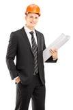 Jonge mannelijke architect in zwart kostuum die helm dragen en bl houden Stock Foto's