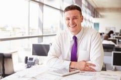 Jonge mannelijke architectenzitting bij zijn bureau, die aan camera kijken Royalty-vrije Stock Afbeelding