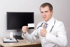 Jonge mannelijke arts die adreskaartje en duimen in bureau tonen Royalty-vrije Stock Foto's