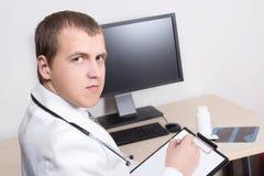 Jonge mannelijke arts die in bureau werken Royalty-vrije Stock Foto's